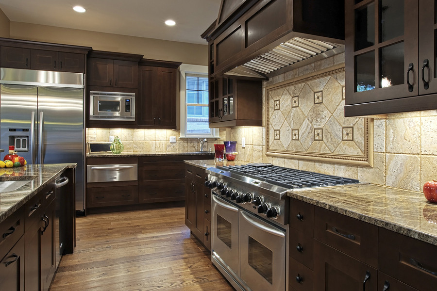 dark kitchen cabinets with a gold top and wood floors