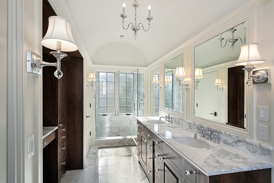European bathroom with light colored fixtures, dark cabinets, and carrara marble