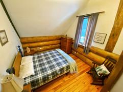 Second floor bedroom with queen bed and closing door