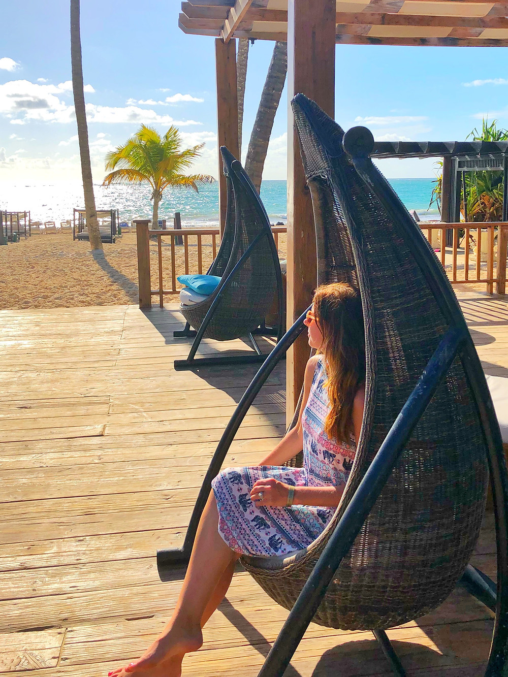 [Image description:] Leah Little sits in a teardrop-shaped chair on a wooden deck at the Punta Cana Princess, a resort in the Dominican Republic. She is a young white woman with light brown hair glowing yellow under the sun. She's wearing a dress with stripes and elephants; it is pink and varying shades of blue on a white material. She is wearing sunglasses. Behind her is a sandy beach with bright blue waters under a clear sky. A few palm trees speckle the background amongst the cabanas on the sand.