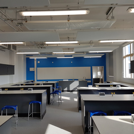 Fully installed plasterboard ceiling and acoustic raft systems at Ilford County High School.