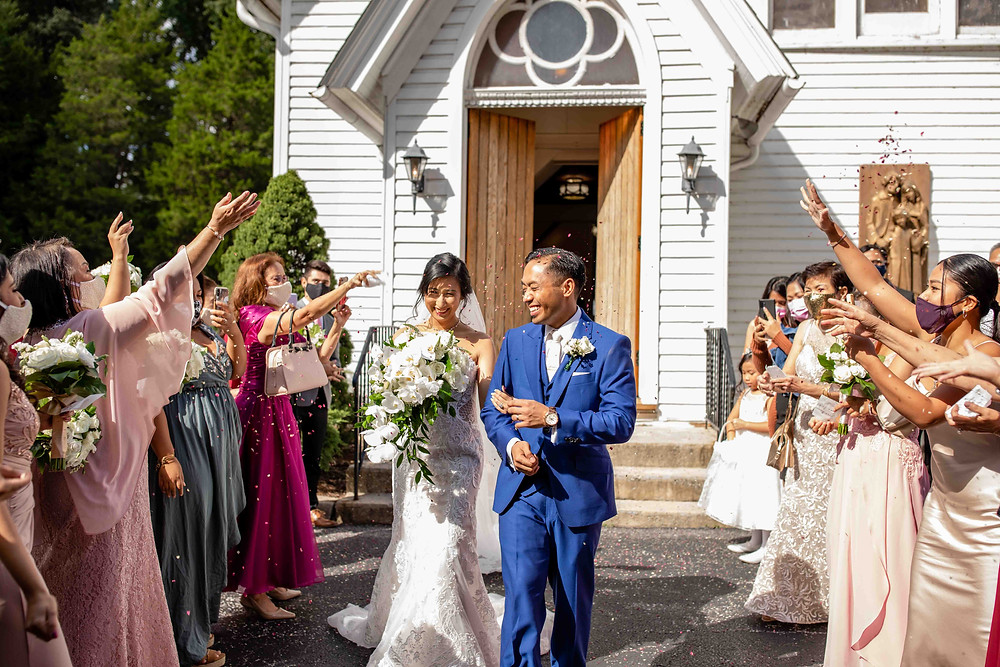 Bride and groom exit Holy Family Catholic Church in Mitchellville, Maryland with confetti on wedding day