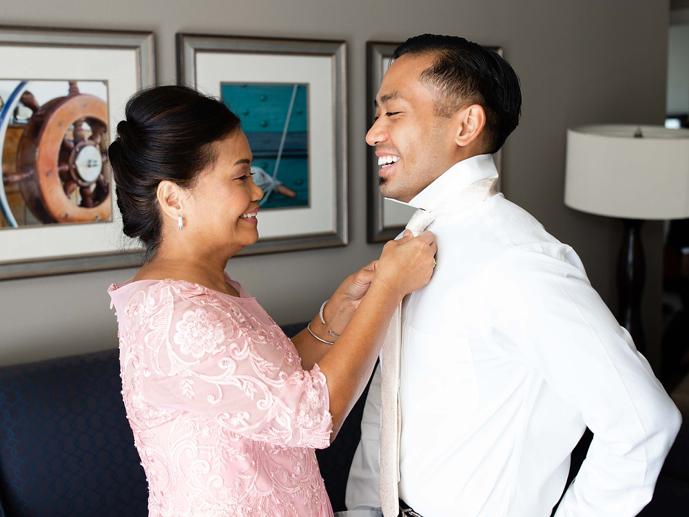 Mom helping son with tie on wedding day at the National Harbor