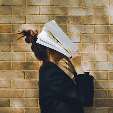 A woman holding a book over her face