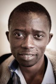 Kemmadou est arrivé de Guinée en 2009 à l'âge de 15 ans. Fuyant la tourmente de son pays, il arrive à Paris un mois de décembre, en plein hiver. Kemmadou découvre le froid et ne connaît personne. Il dort dans le métro. Cherchant de l'aide auprès de la communauté africaine parisienne, une femme sénégalaise l'héberge pendant quelques temps, puis il est pris en charge par l'Aide Sociale à l'Enfance (ASE). Il est hébergé en foyer et à sa demande scolarisé. Grâce au travail qu'il trouve en parallèle à ses études, il obtient en janvier 2013 un titre de séjour salarié renouvelable tous les ans, ce qui signife que le jour où il n'a plus de travail, il se retrouve à nouveau « sans-papiers ». Ses revenus ne sont pas énormes et l'aide fnancière ainsi que le logement de l'ASE vont s'arrêter en juin. Kemmadou voudrait pourtant continuer les études de métallerie qu'il a entamées. Il rejoint la troupe des jeunes peu de temps après sa création.