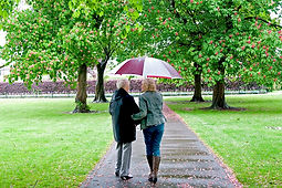 Lady and volunteer walking with umbrella