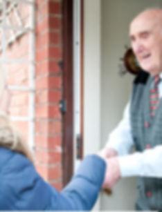 Man welcoming volunteer at door