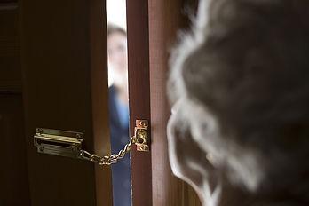 Elderly lady looking though door