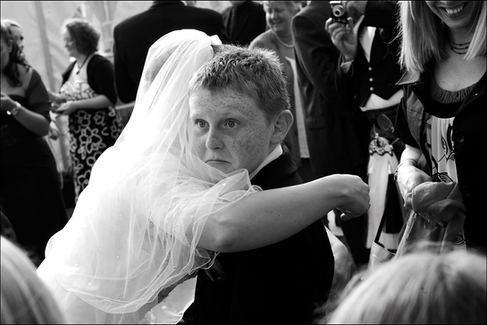 Little boy freezes when bride hugs him