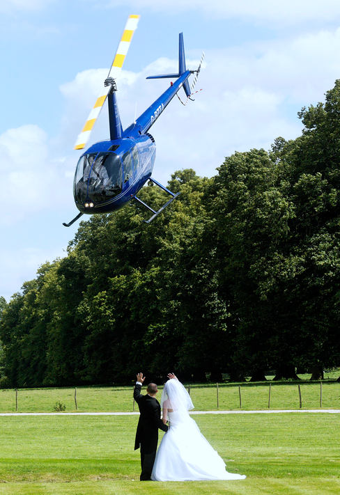 Bride and groom wave goodbye to helecopter