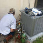 Worker Fixing a Heat Pump Air Cond
