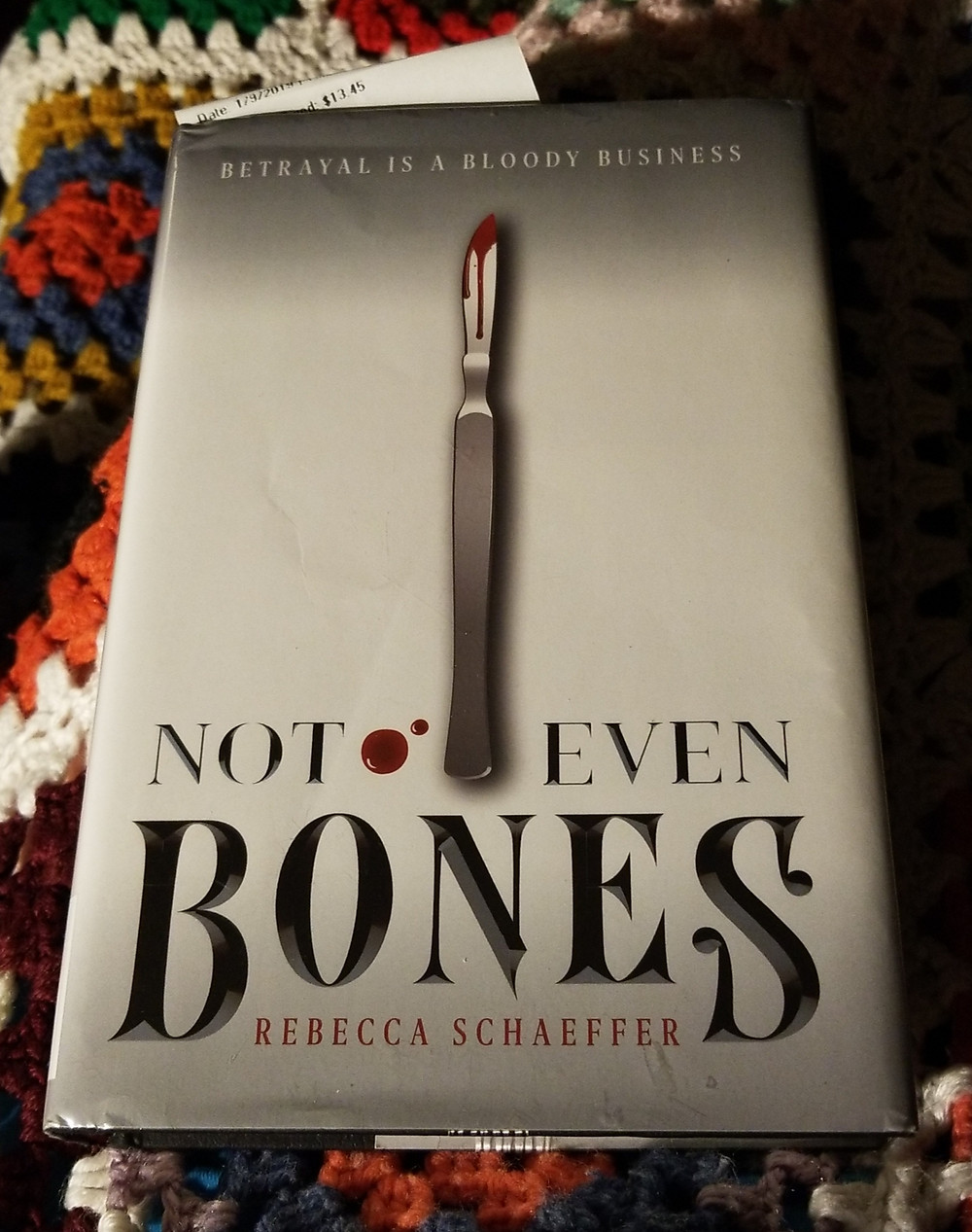"book cover of ""Not Even Bones"" on crocheted blanket."