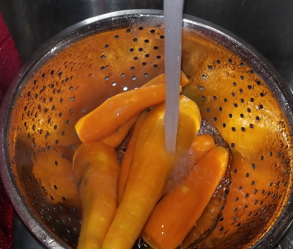picture of water running over a colander with carrots in it