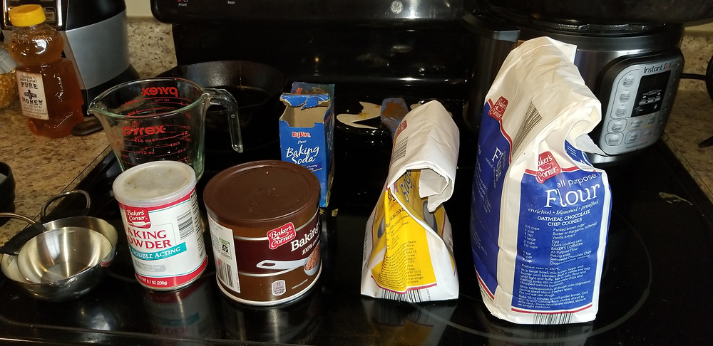 On the left are stainless steel measuring cups, followed by baking powder, baker's cocoa, sugar, and flour in the front row. In the back row from left to right, honey, 2 cup glass measuring cup, baking soda, trivet, and an instant pot