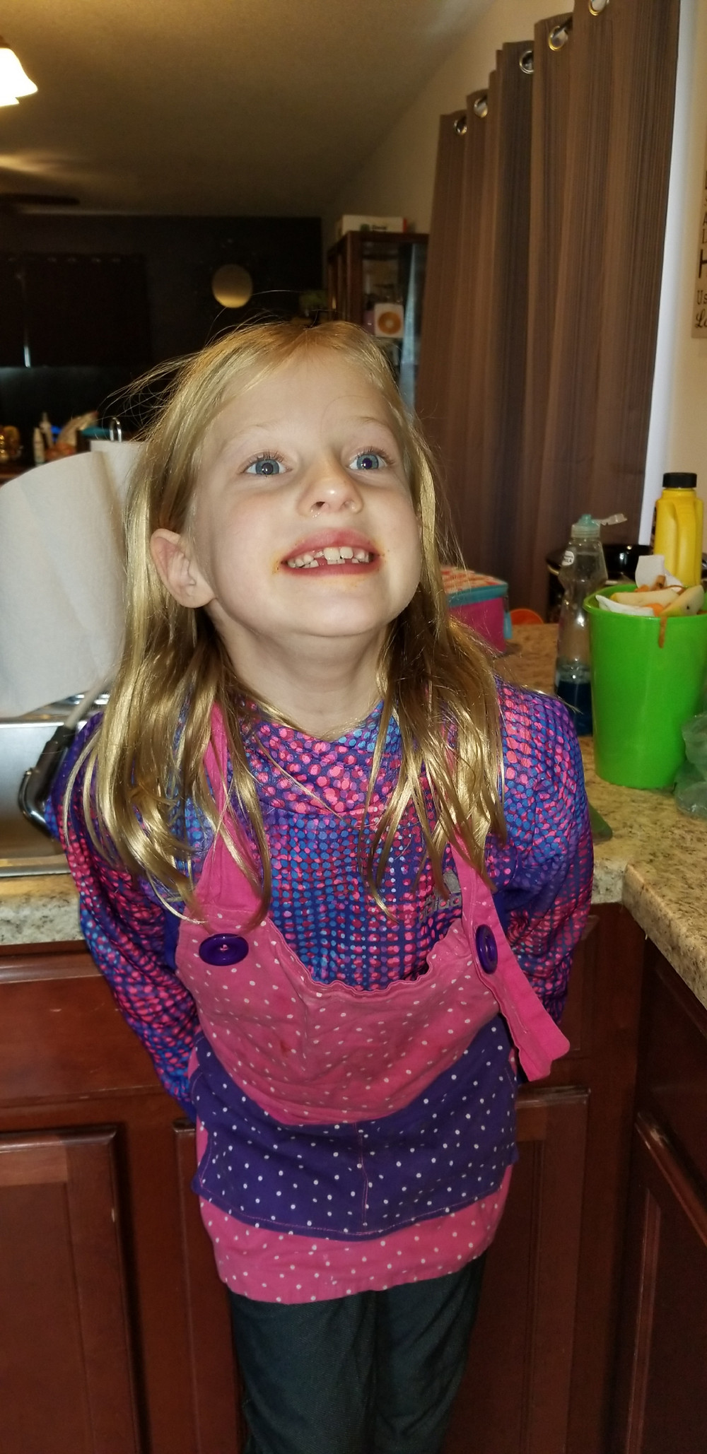 An 8 year old girl, wearing a pink and purple apron. She has blond hair, blue eyes, and her teeth are not all the same size due to some adult teeth interspersed with her baby teeth.