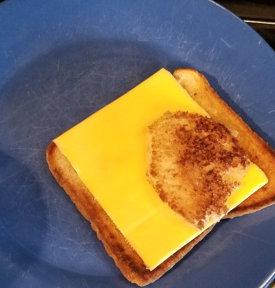 blue plate with slice of toasted bread with cheese and small circle of bread on top