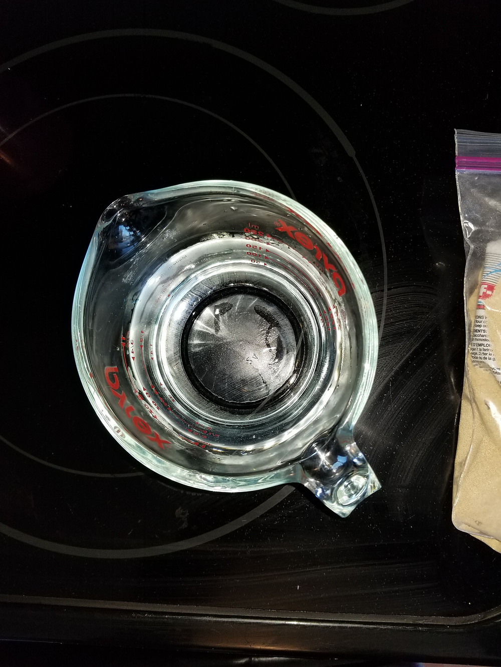 glass Pyrex measuring cup filled to 1 cup mark with hot water sitting on a black stove top next to a bag of yeast.