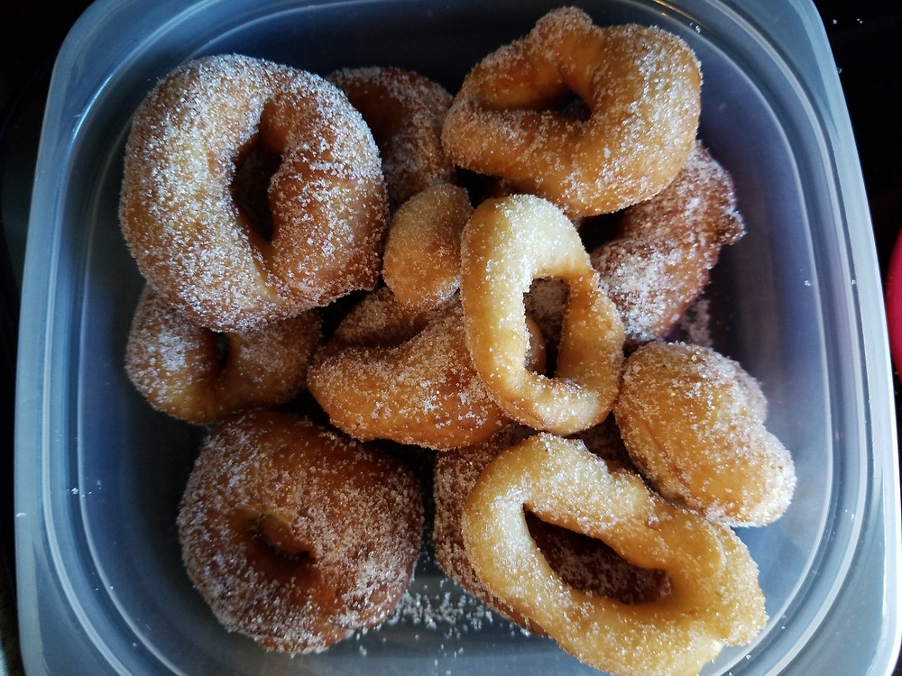 clear plastic container holding homemade doughnuts dipped in sugar.