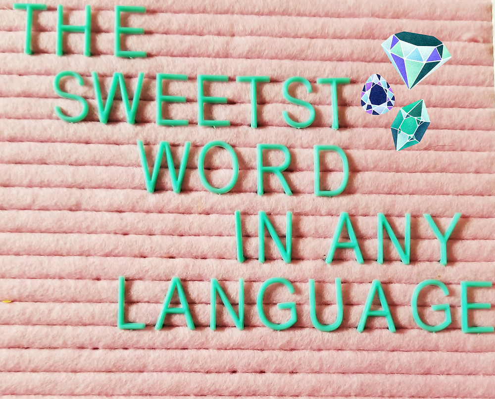 "Sign with letters spelled out to say ""The Sweetest Word In Any Language"" with a pink background and turquoise letters. To the right are three diamonds."