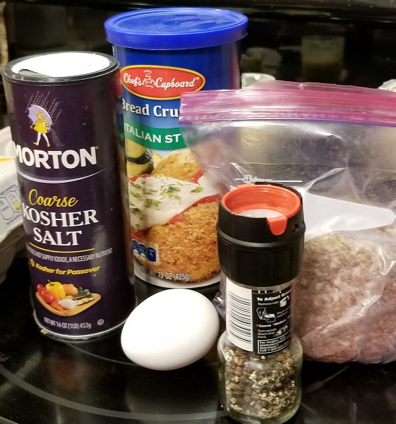 from left to right, kosher salt, bread crumb cylinder, egg, pepper, ground beef on black stove