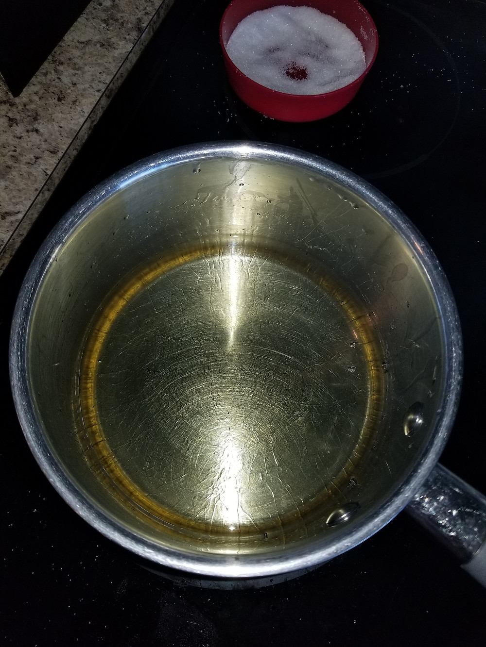 In the front, a sauce pan full of oil to fry the doughnuts. In the back, small red bowl with sugar.