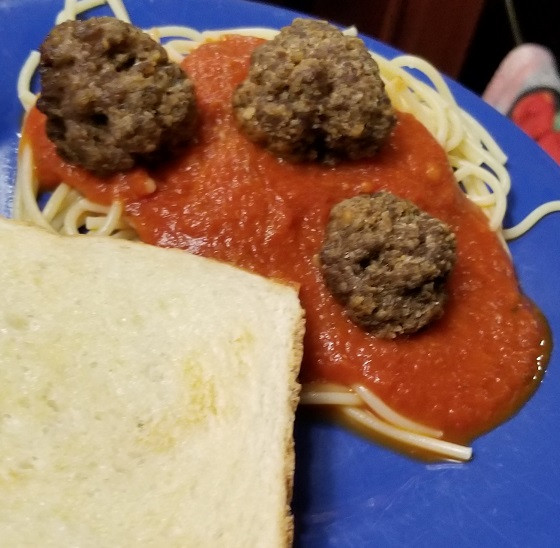 blue plate with Texas Toast, spaghetti noodles covered in marinara sauce and three homemade meatballs on top