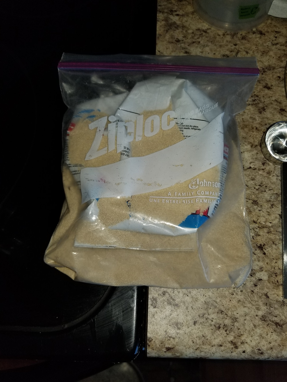 Ziploc bag of yeast straddling the stove and counter top