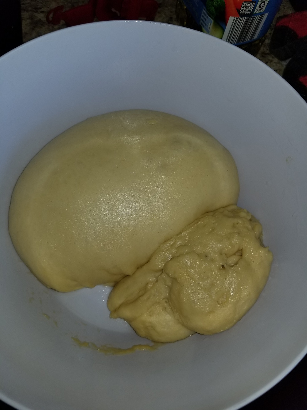 white inside of a bowl with dough on the inside that has risen for 1 hour.