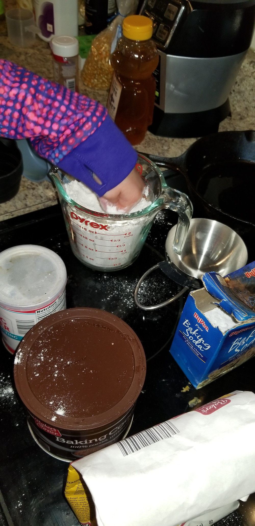 overcrowded counter with sprinkles, honey, Ninja blender, girl's arm in a liquid measuring cup filled with flour