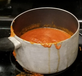 pan on stove with red marinara sauce
