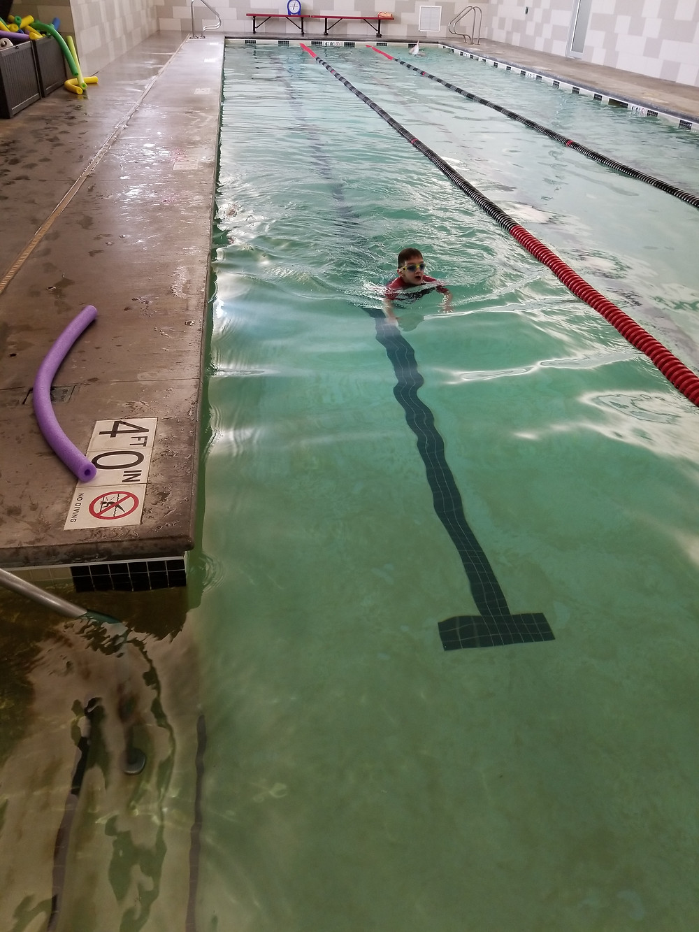 The Midwest Athletic Club's pool area in Cedar Rapids, Iowa. Bin of pool noodles in yellow, green, and blue on the left, cement pool deck around a three-lane indoor swimming pool.