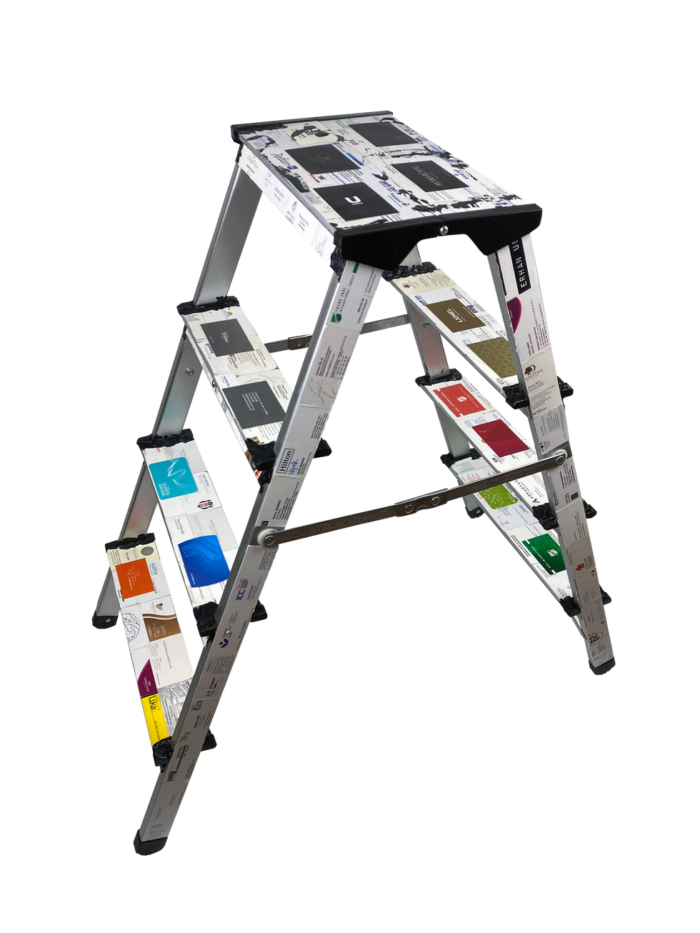 Disidentification / v 2020 / 35x88x88 cm / Paper, acrylic on aluminum / Aluminum ladder, covered with business cards. The black weld spots symbolize the greed of power and promotion in business. On top, there is only darkness and disidentification.