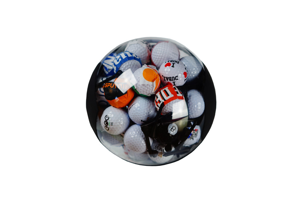 the Crumpled Newspaper / 2018 / Ø20 cm / Acrylic, plastic, golf balls / Criticism on sports' distracter effect on the society. Soccer- ball-symbolization-sphere holds the golf ball collection and crumpled newspaper / news channel logos.