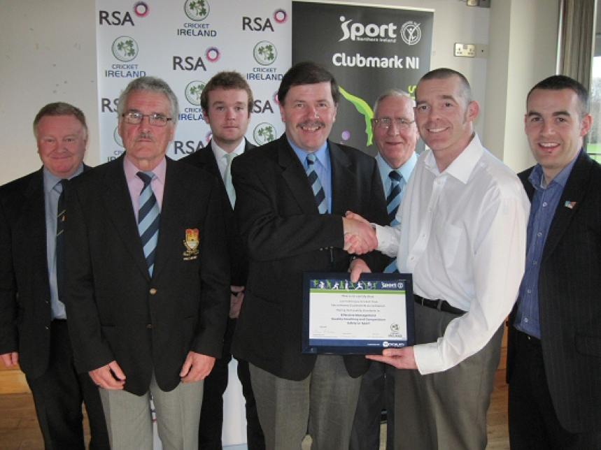 Carrickfergus Vice President and Northern Cricket Union Chairman Roger Bell receives the Club Accreditation Scheme certificate from Cricket Ireland's Club Development Manager Tim Simmonite. Also included are Sport Northern Ireland Performance Consultant Simon Toole and other representatives from the Carrickfergus club including Ireland international Paul Stirling, President Leslie Thompson, and Committee members Brian Stirling and Wallace Luney.