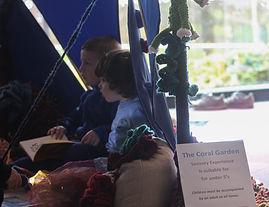 Children sitting inside the Coral Garden installation