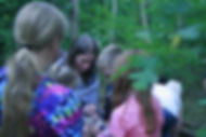Children looking at an object held by adult in nature