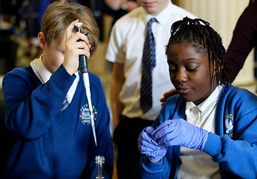 Two school pupils, one with a large pipette and aother with gloves on