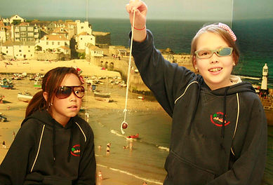 Two pupils with broken sunglasses on, one holding a conker on a string