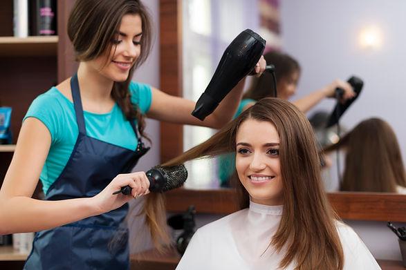 female-hairdresser-using-hairbrush-and-h