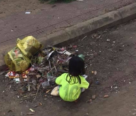 Homeless child in Cambodia looking for food in garbage