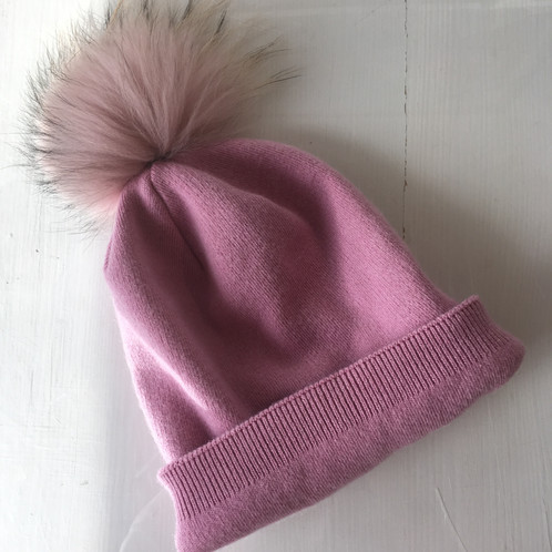 6444bba3947 A pink hat with turn up trim and detachable faux fur pom-pom. Grey Facebook  Icon