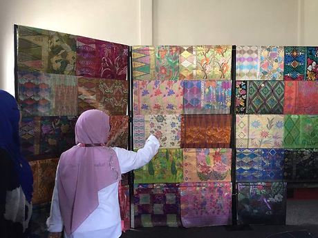 A broker is showing the handmade songket in her house.