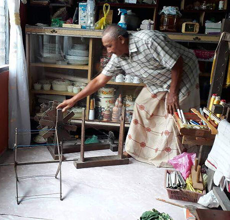 A village resident is showing his kit for spinning.