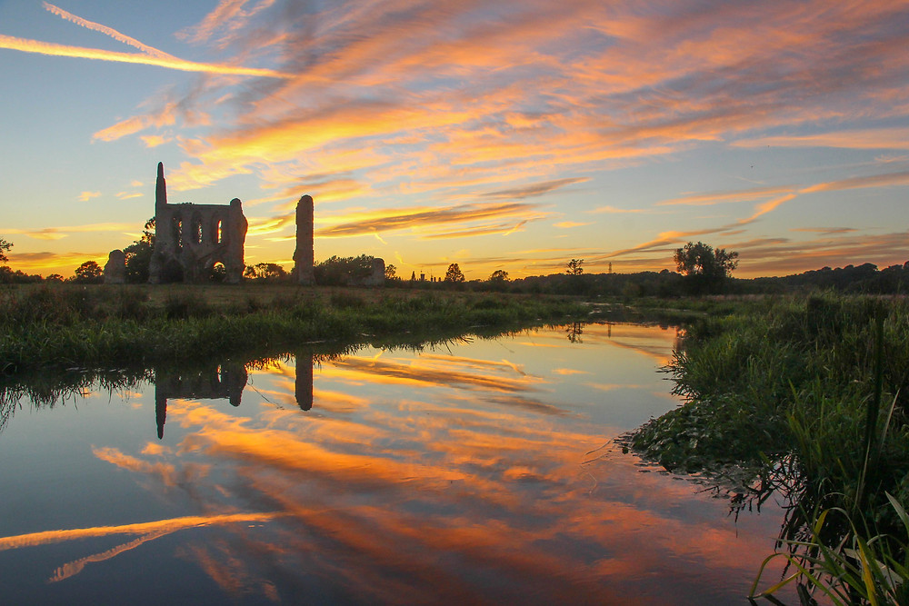 The ruins of Newark Priory by the River Wey at sunset