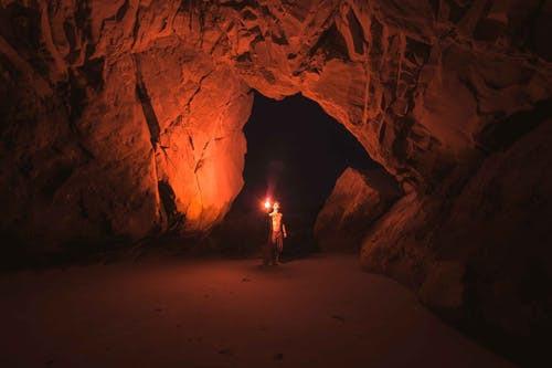 © Pexels.com - un homme éclairant la caverne
