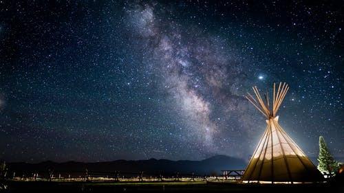 © Pexels.com - Photo d'un ciel étoilée, avec la voie lactée et un tipi