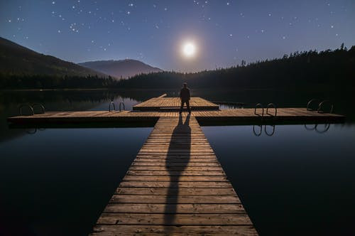 © Pexels.com - Homme regardant la lune basse sur l'horizon, faisant dos à son ombre.