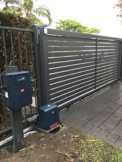 Solar powered sliding slat gate