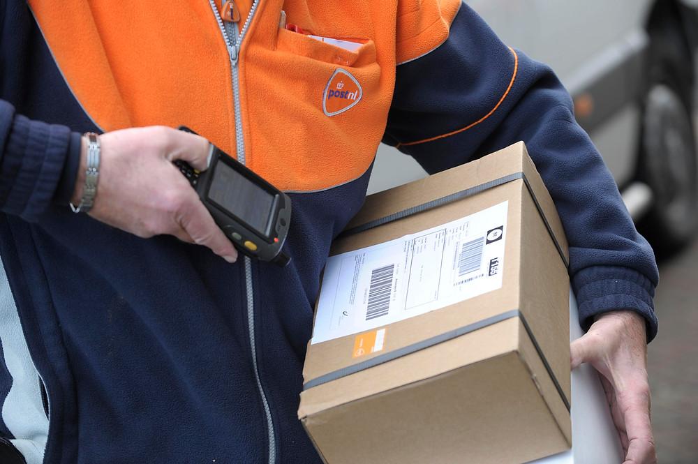 Postbezorger die een pakketje scant