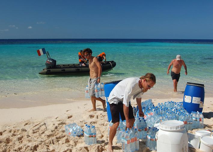 De nombreuses rotations en zodiac, entre La Moqueuse mouillée au large, et la plage, sont nécessaires pour décharger le matériel de la mission : 1 tonne d'appât empoissonné, 300 bouteilles d'eau, 200 boites de conserve…
